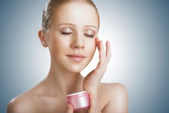 a woman applying skin cream to her face